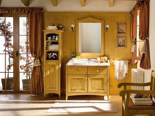 Vista di un bagno in arte povera arredato con mobiletto in legno chiaro con lavandino incastonato con rubinetteria in ottone e grande specchio.