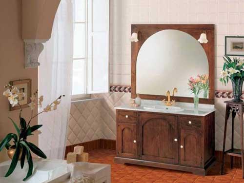 Vista del mobile in legno con lavandino incastonato in ottone all'interno di un bagno arredato in arte povera, al di sopra un grande specchio come accessorio.