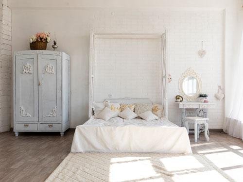 Vista di una camera da letto arredata in stile shabby chic con grande letto matrimoniale con testata a mò di cornice di legno bianca. Vicino una toletta dai colori bianco e panna e un armadietto recuperato dal colore azzurrino.