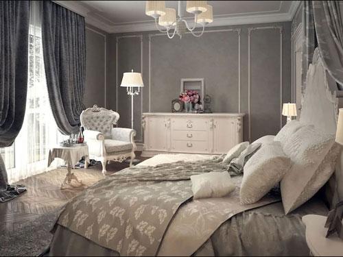 Camera da letto arredata in stile shabby chic con tinte scure, in primo piano un letto matrimoniale con svariati cuscini, sullo sfondo una poltrona classica bianca e una cassettiera rosa antico xon fiorera adagiata sopra.