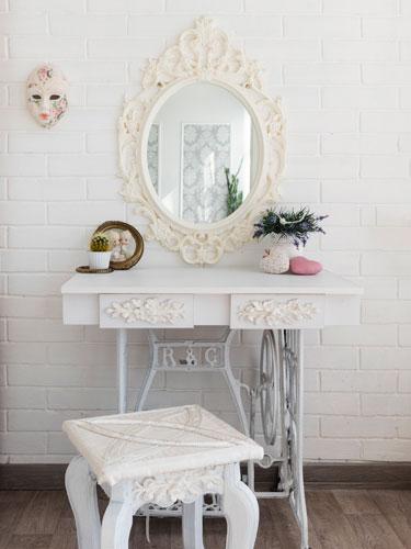 Vista di una toletta da camera in perfetto stile shabby con colori bianco e panna, grande specchio e sgabello ornati con fantasie classiche