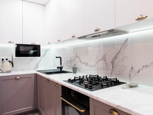 Vista di una cucina angolare con ante bianche in stile classico con fornello e lavello in alluminio nero