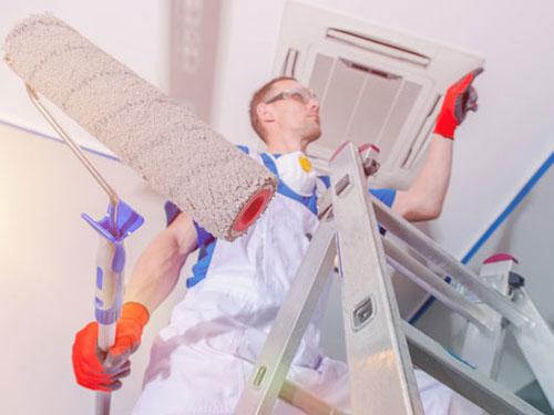 Operaio su uno scaletto intento nelle finiture durante una ristrutturazione