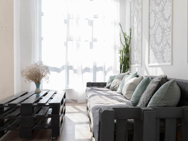 Vista di un salone con arredi in tinte scure e tendaggi bianchi che rendono l'ambiente molto luminoso
