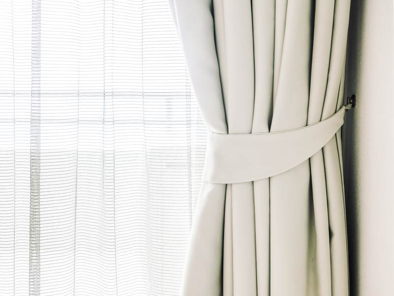 Immagine di una tenda color panna appena installata avanti ad una finestra
