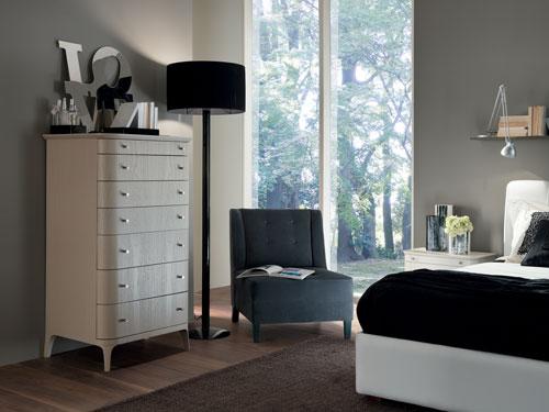 Vista di una cassettiera classica con lampada e poltroncina di fianco