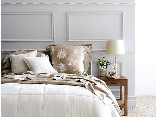 Vista di un letto senza testata con cucnini poggiati al muro con di fianco un tavolino in legno con piccola piantina e una lampada