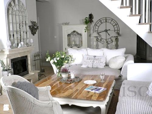 Vista di un salone arredato in stile provenzale con tinte bianche e tavolo in legno chiaro