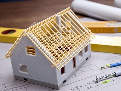 immagine raffigurante un modellino di casetta su una scrivania con di fianco righelli e progetti arrotolati