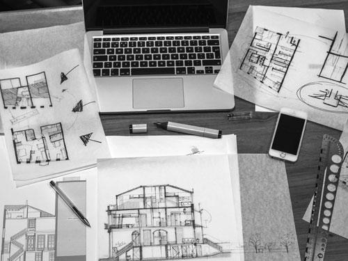 foto in bianco e nero raffigurante una scrivania coperta da fogli con bozze di progetti edili