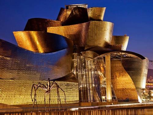 Vistaesterna notturna del Guggenheim Museum di Bilbao illuminato con luci calde