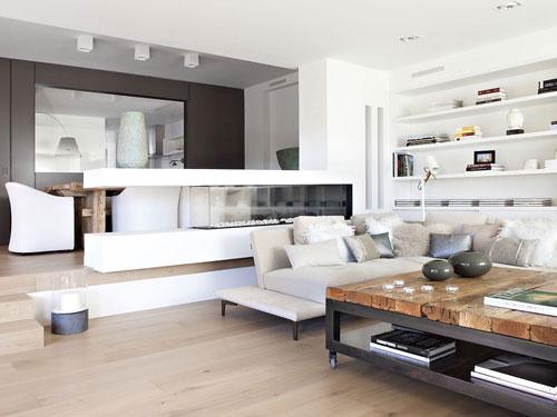 Vista di un salone in stile moderno con bancone bianco in muratura a dividere due ambienti, grande specchio sullo sfondo e in primo piano tavolino con piano in legno e piedi in ferro battuto