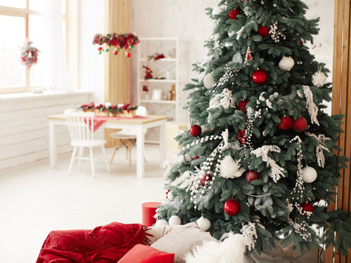 Vista ravvicinata di una alberello di natale e sullo sfondo una cucina addobbata con fiori eossi e copritavola natalizio