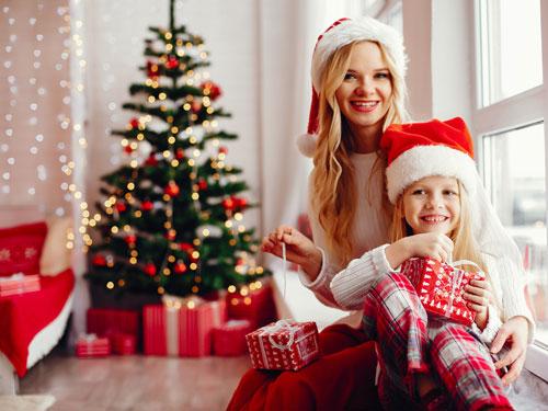 Foto di due sorelle che aprono i regali di natale, sullo sfondo un albero di natale dai colori rosso ed oro
