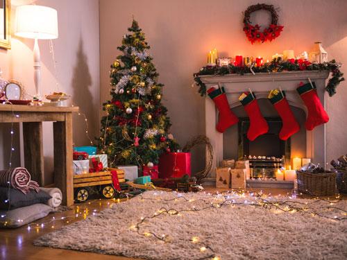 Vita di un salone con albero di natale nell'angolo, di fianco un caminetto con calze rosse appese in attesa di essere riempite di doni