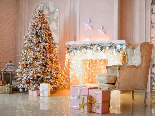 Vista di un salone con albero di natale imbiancato e camino con led luminosi addobbati a festa