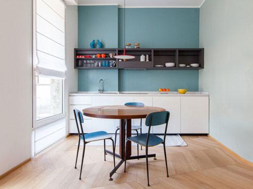 Vista di una cucina piccola con tavolino rotondo a tre posti e cucina lineare bianca su parete azzurrina