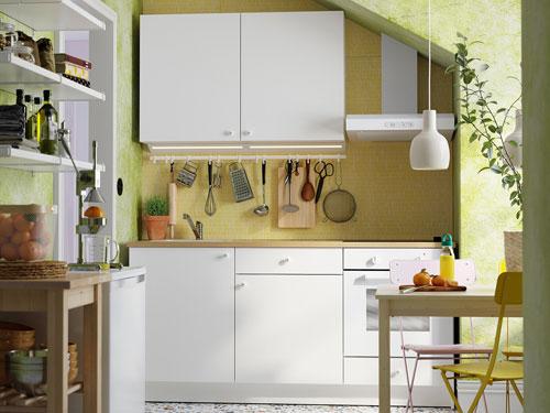 vista di una cucina piccola con spazi irregolari con toni del bianco in un ambiente molto green