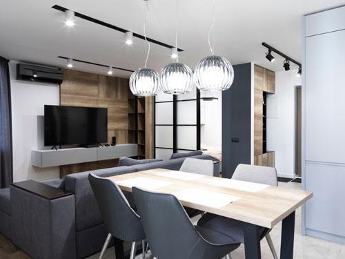 Salone in stile contemporaneo con tavolo e sedie di design, e lampadario a tre sfere