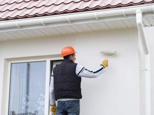 Operaio intento nella verniciatura di una fcciata esterna ad un abitazione