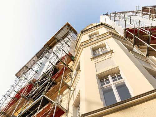 Vista dal basso di un palazzo con ai lati delle facciate impalcature per la ristrutturazione delle facciate