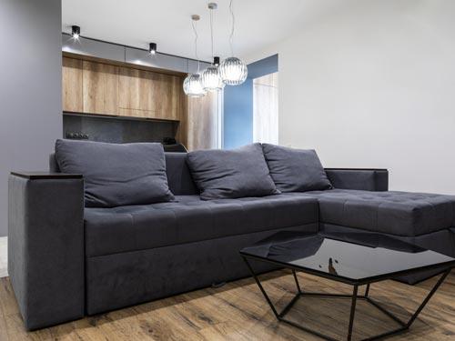 Salone in stile classico moderno con sofà blu e inserti in legno con tavolino in vetro classico.