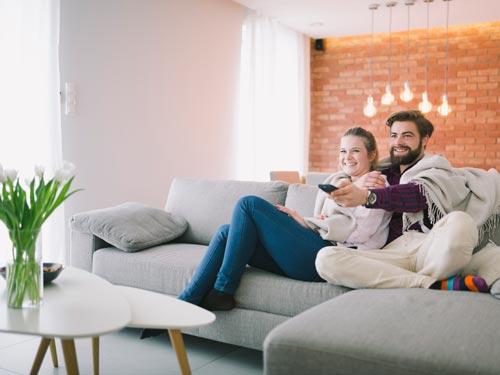 Coppia seduta su di un sofà intenti a guardare la tv nel loro soggiorno arredato in stile classico moderno