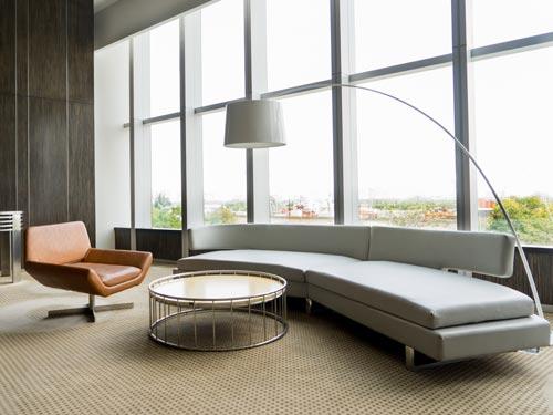 Salone in stile classico moderno con divano lungo e poltrona in pelle.