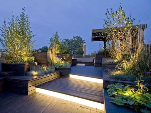 Vista di un grande terrazzo con illuminazione a terra con fioriere