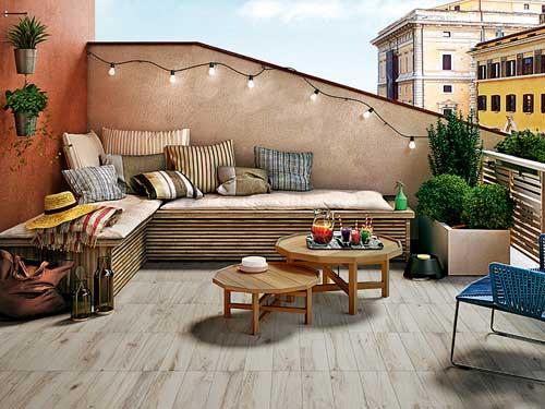 vista di un terrazzo arredato con salottino ad angolo con doppio tavolino in legno
