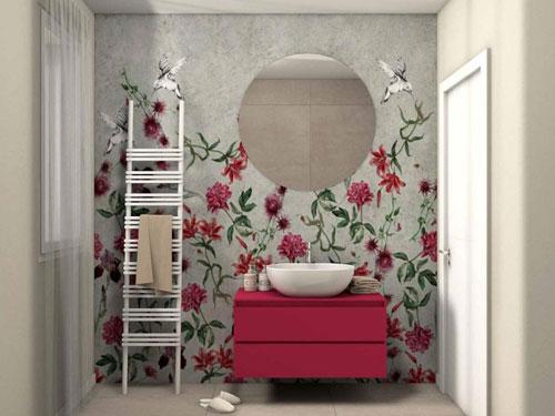 Vista di un lavello da bagno su mobile rosso con grande specchio rotondo sopra su parete decorata con disegni floreali