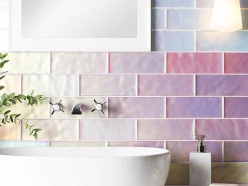 Vista di un lavello da bagno bianco davanti ad una parete rivestita con piastrelle multicolore che vanno dall'azzurro al giallo fino al rosa