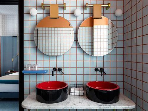 Vista di un doppio lavello da bagno nero e rosso su piano in marmo con al di sopra specchi a padella con attacchi a parete in ottone
