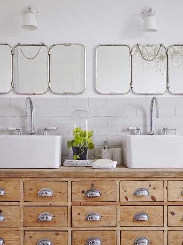Vista di un doppio lavello da bagno su mobiletto in legno con tripli specchi e faretti a muro per illuminare