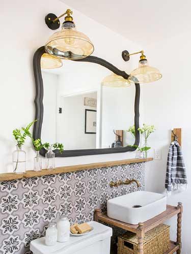 Vista in diagonale di uno specchio da bagno incorniciato con lampade classiche a muro
