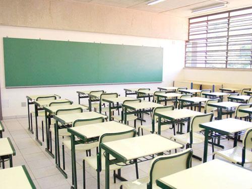 classe di una scuola con file di banchi davanti ad una lavagna