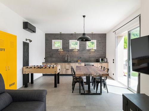 Vista di un open space salone cucina in stile industriale con elementi in legno e ferro battuto