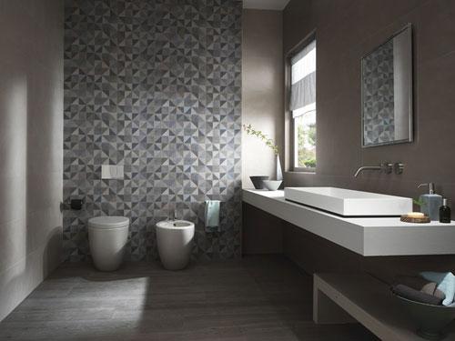 bagno con sanitari filomuro e parete con rivestimenti scuri