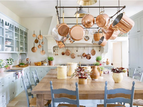 Cucina in stile country con grande tavolo in legno e mobili e sedie celesti
