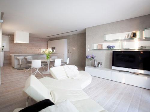 Vista di un open space arredato in stile minimal con parete attrezzata bianca e divano in pelle bianca