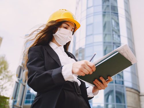 Architetto su cantiere con mascherina e casco di sicurezza