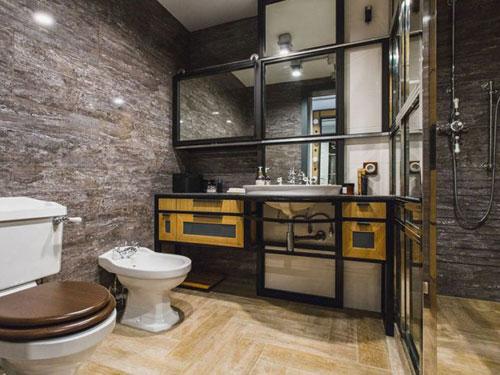 Bagno in stile industriale con sanitari classici e mobile in ferro battuto