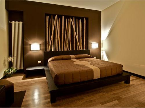 Camera da letto in stile etnico a tema orientale con letto a base di legno nero e testata con canne di bambù