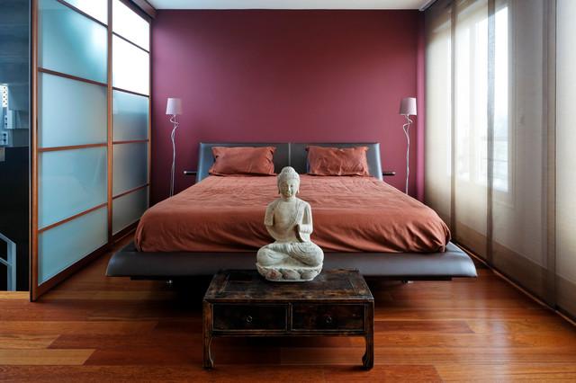 Camera da letto in stile etnico con statua di derivazione orientale ai piedi del letto con i colori legno e rosso