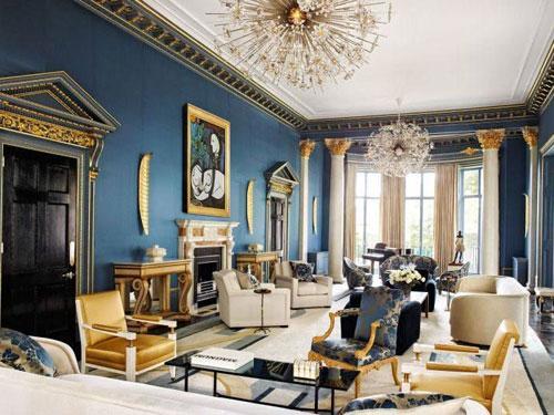 ampio salone arredato in stile barocco con doppio lampadario di cristallo, tavoli in vetro nero e poltrone con fantasie oro e blu