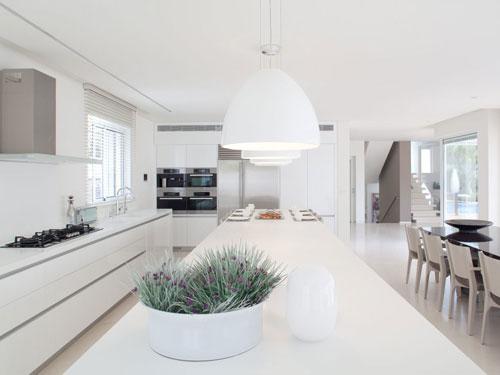 Cucina con i toni tenui del bianco e beige arredata in stile minimal chic